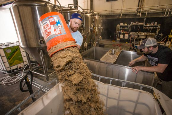 Memphis Made assistant brewer Alex Ball emptying the mash tun