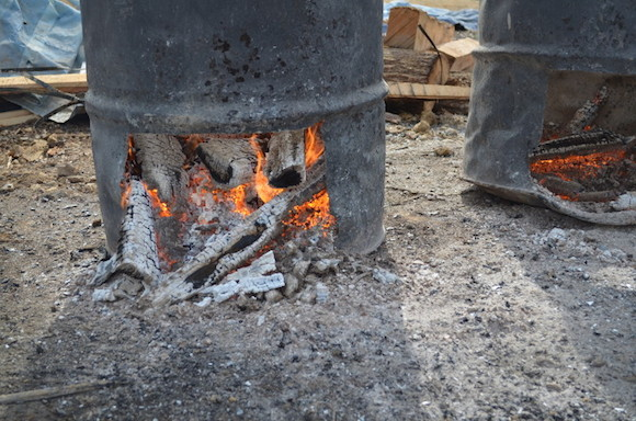 Wood burns down to make coals in a barrel outside the smokehouse at Latham's Meat Company in Jackson, Tenn.