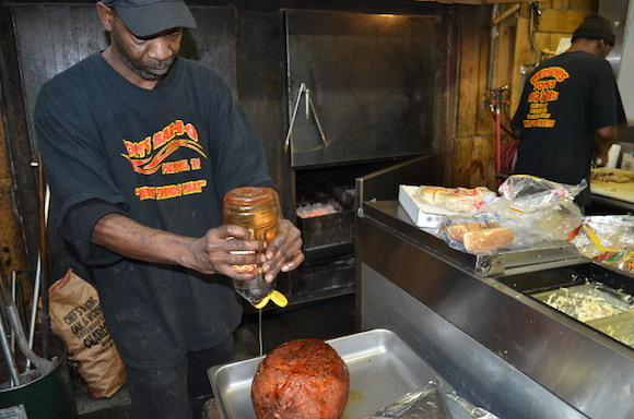 An employee at Tom's Bar-B-Q on Getwell squeezes honey onto a ham the restaurant is about to smoke.