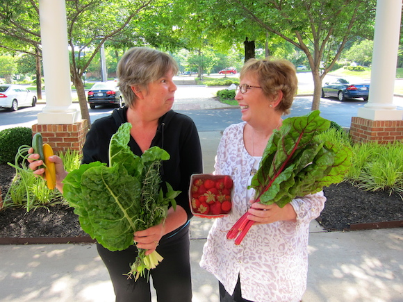 CSA subscribers Lorinda Hill (left) and Sandra Fortson compare notes on this week's haul, which features Swiss chard, strawberries and garlic scapes