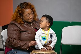 A parent and child make music in a drum circle at the Knowledge Question Universal Parenting Place in South Memphis. (Submitted)