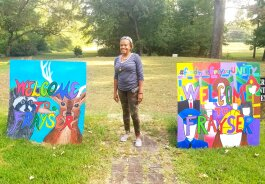 Frayser Local Arts Festival organizer Lurlynn Franklin stands next to two of five 'Welcome to Frayser' paintings. She designed the signs as paint-by-numbers and more than 700 Frayser residents had a hand in filling them in. (Arkwings Foundation)