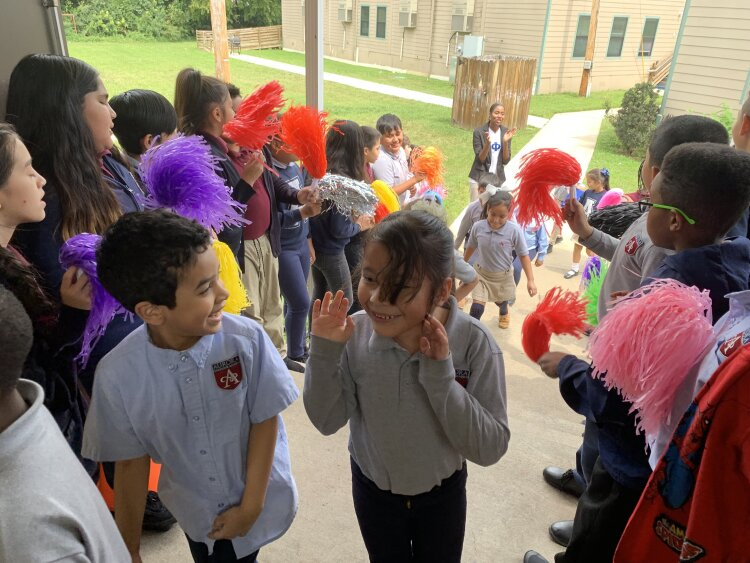 Fifth-grade scholars cheer on K-2 scholars as they head into their Friday Community Meeting. Gonzalo Munguia Lopez Jr. (center, left) and Yoselin Garcia (center, right) share an excited smile. (Cat Evans)