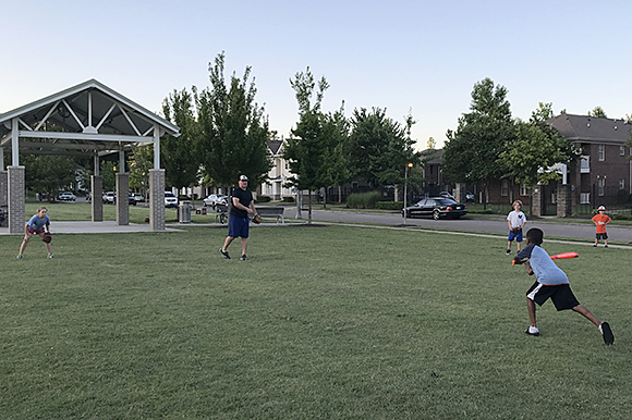 Nathan Sawyer pitches to his neighbor in an impromptu game of baseball at Uptown Park.