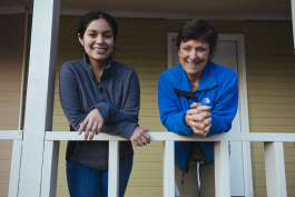 Magaly Cruz (L) and Joni Laney on the porch of a property that was previously blighted. The land trust worked with Neighborhood Preservation Inc. to report the house to Code Enforcement and within one month it was in compliance. (Ziggy Mack)