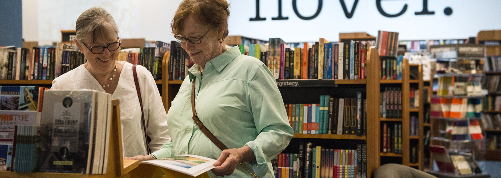 Tes Herman, left, and her cousin Leslie Herman look at a book of Freida Hamm paintings at Novel bookstore in East Memphis. <span class='image-credits'>Brandon Dill</span>