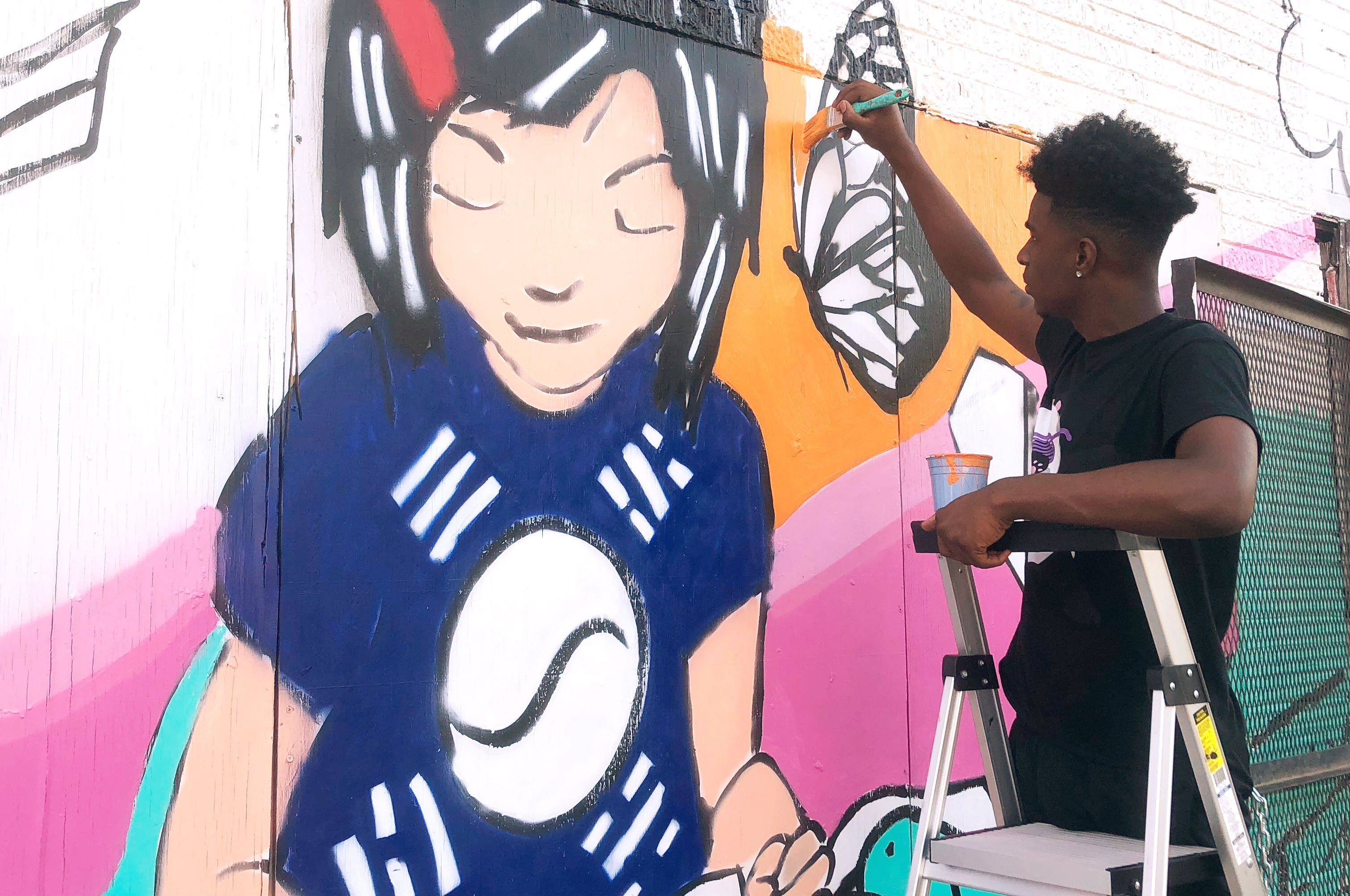 Donte Davis works on a section of the You's Grocery mural depicting store owner Ae An Sartain as a child when her father first opened the store. The artists based the mural on Sartain's memories and neighborhood history. (A.J. Dugger)