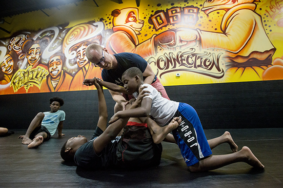 Lucas Trautman, top, demonstrates grappling technique with students Keyveyoun Chandler, 14, left, and Eric Booker, 11, at his Stardust Jiu-Jitsu studio in Binghampton. (Brandon Dill)