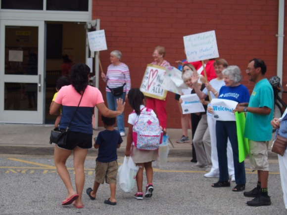 Neighbors, faith leaders and advocacy groups greet immigrant families arriving at Brewster Elementary School on the first day of class in Memphis