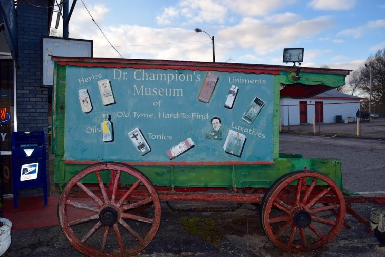 "A wooden medicine wagon advertises ""Dr. Champion's Museum of Old Tyme, Hard to Find Tonics"". (Rachel Warren)"