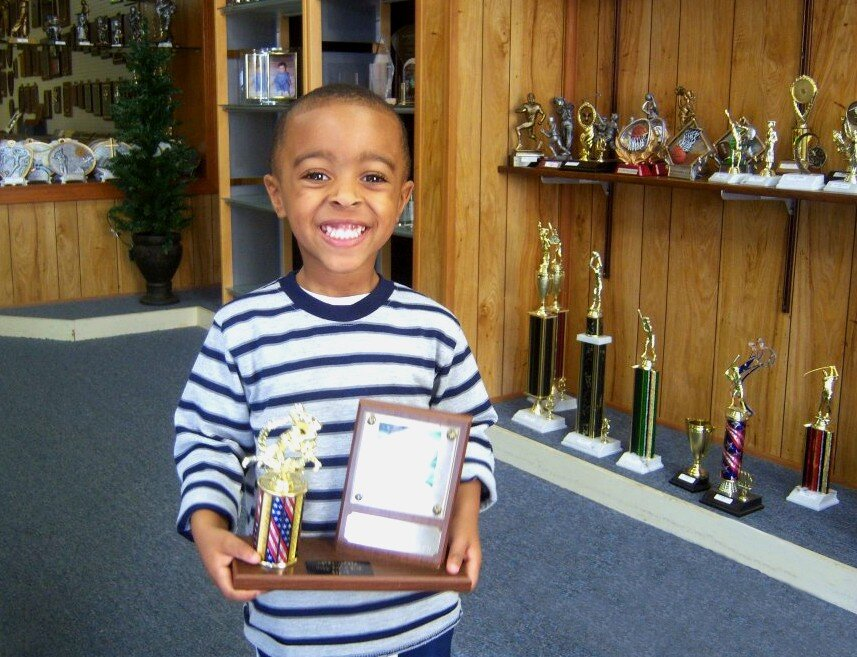 A child proudly displays an award at C & J Trophy and Engraving, located at 3444 Park Avenue in the Orange Mound-University District area. The business has been open since the 1970s. (C & J Trophy and Engraving)