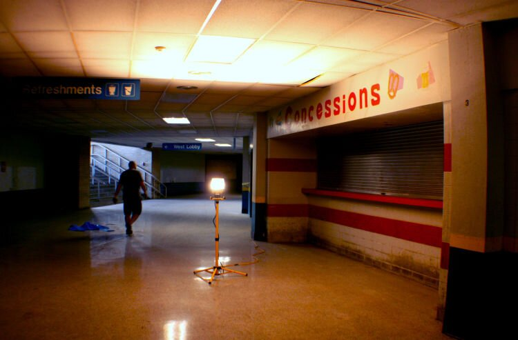 Chooch Pickard, the Coliseum Coalition's vice president, walks the lower-level corridor near a shuttered concession stand. (Shelda Edwards)