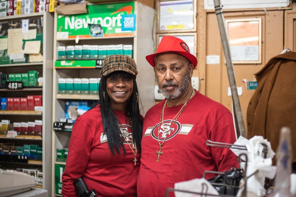 The owners of the Shop & Save pose behind the counter of their South Memphis corner store. (Malik Martin)