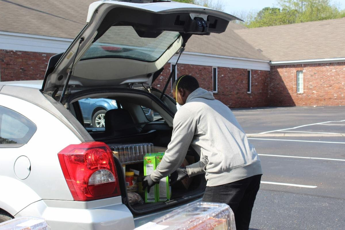 A volunteer with the Neighborhood Christian Center packs a family's car with a week's worth of meals. NCC is one of the organizations that has received funding from the Mid-South COVID-19 Regional Response Fund. (Submitted)