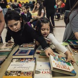Children pick out a book at Desayuno Con Libros held monthly at Gaisman Community Center. (Desayuno Con Libros)