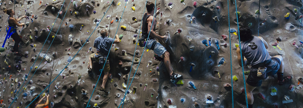Climbers scale a rock wall located Uptown at the BRIDGES facility.