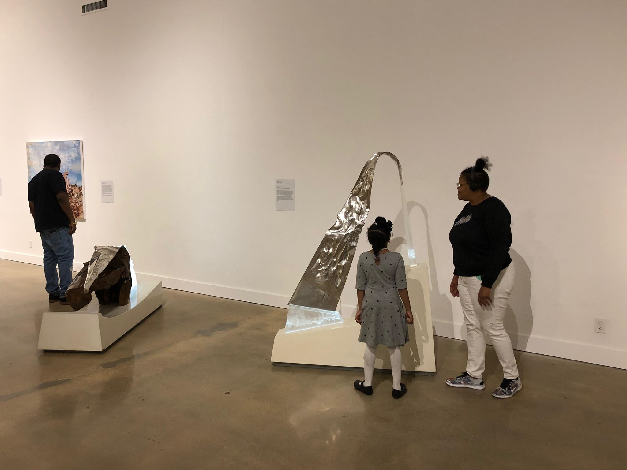 "Megan Savare looks on as daughter Christina shares her favorite piece of the ""Dear Artist"" installation - a sculpture by John Carl Marshall titled ""Glacier"". (Scarlet Ponder)"