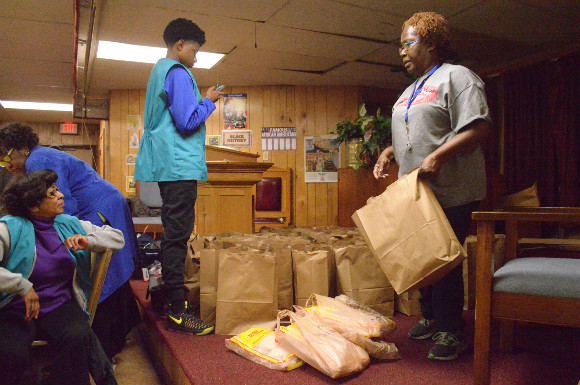 Friendship Baptist parishioner Verdis McNutt assists with distributing much needed groceries to Klondike Smokey City residents who show up the church's Friendship Feeding Program.