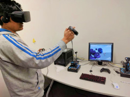 A VR user in action. What is displayed on the screen is a two dimensional representation of what is shown in a full three dimensions in the headset. Photo courtesy of Memphis Game Developers.