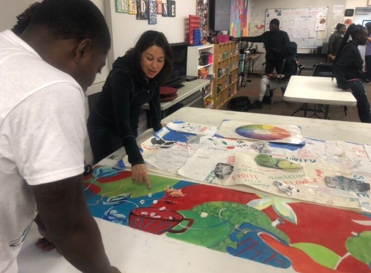Yancy Villa-Calvo and Brandon Zuber (left) discuss design elements on a working draft of the mural that will be installed on the side of Whitten Brothers Hardware in Orange Mound. (A.J. Dugger)