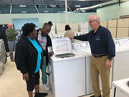 The Oasis Appliance store's strategic manager, Dana Driver (R), assists customers in selecting a new washing machine. (A.J. Dugger)