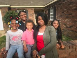Shamika Williams poses with her four children outside of their home in Raleigh. In fall 2018, Williams fled an abusive relationship and stayed with her kids at the YWCA's domestic violence shelter. (Cole Bradley)