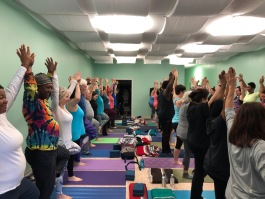 A diverse group of students hold a pose at Yolandrea Clark's Any Body Yoga studio in Midtown Memphis. (Shelby Black)