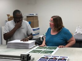 Al Harville (L) and Allison Hancock work together to finalize the design and layout on a client's order. (AJ Dugger III)