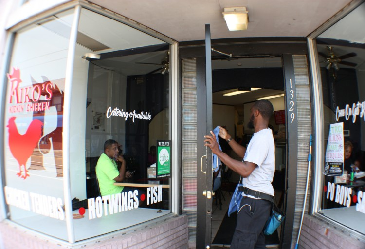 Walter Clark, owner of Outstanding Touch window services, puts the finishing touches on the door of Riko's Kickin Chicken, located at 1329 Madison Avenue. (Cole Bradley)