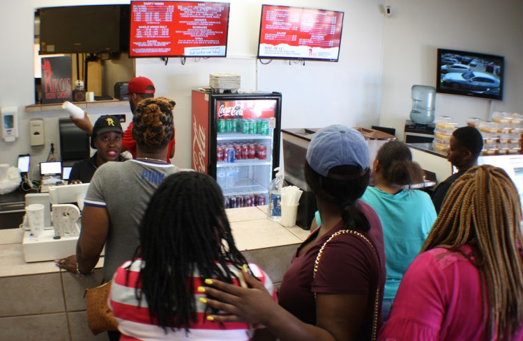 Tiffany Wiley serves a line of hungry customers. Wiley co-owns Riko's Kickin Chicken with her husband Mariko Wiley. (Cole Bradley)