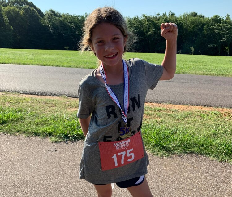 Juleann Roberts flexes her muscles after taking first in the youth division of The Hagar Center 5K Fun Run. (Ashlei Williams)