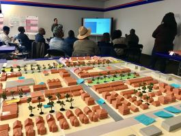 Residents and other stakeholders hear the results of the three-day design charrette to reimagine Whitehaven Plaza. In the foreground, the model of Whitehaven Plaza shows existing structures in gray alongside new buildings, greenspaces and amenities s