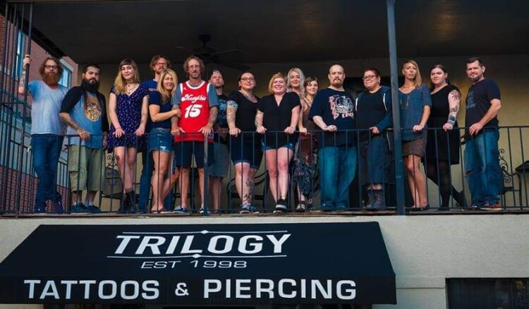 The staff stands on the balcony of Trilogy Tattoos and Piercing. Owner Richie Jarvis stands left of center in the red #15 jersey. (Submitted)
