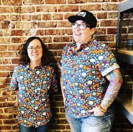 High Ground publisher and community engagement manager, Emily Trenholm (L), and managing editor, Cole Bradley (R), pose in matching shirts on an Accidental Uniform Day. (Belltower Artisans)
