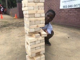 A young South Memphis resident plays with a giant Jenga set. (Shelda Edwards)