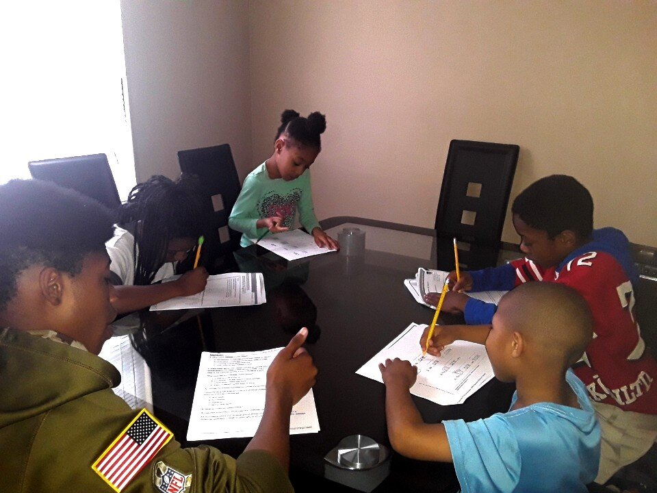 The Covid-19 crisis has caused Christina Ueal's dining table to become a classroom. Her five children, ages five to 15, work on packets provided by their schools at their home in Frayser. (Submitted)