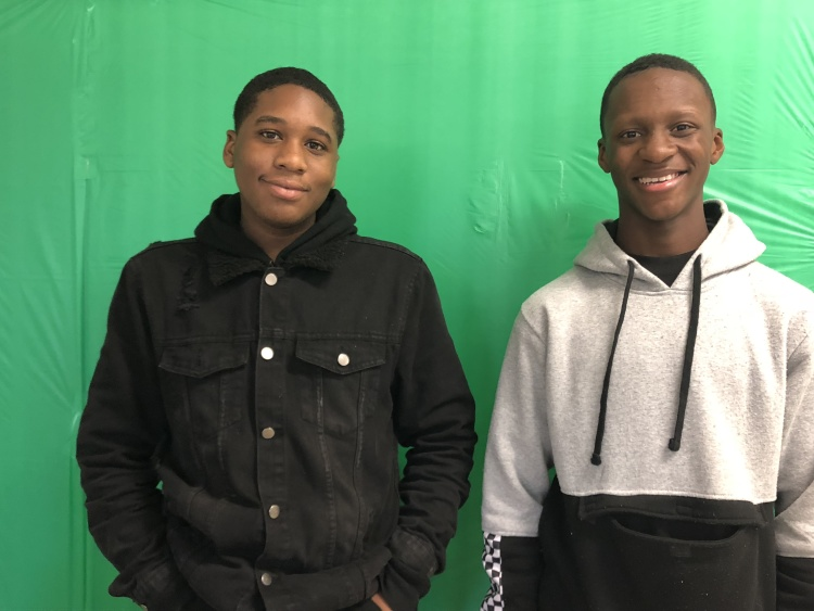 Staff writer and editor Nickcolus Blakemore (L) and staff writer Marquavious Wray pose in front of the new KHS Live! greenscreen. (Flying Falcon)