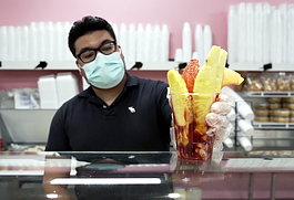 An employee of La Michoacana ice cream and paleta shop serves up a fruit cup with tajin. (Forever Ready Productions)