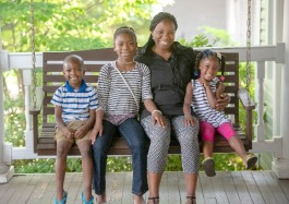 Hope House client and HIV advocate Latrina Moore and her three children pose for a portrait on the Hope House swing. Her two youngest children have attended Hope House's daycare and pre-K. (Greg Campbell)