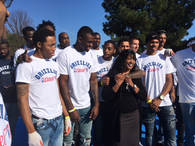 Dr. Andrea Miller, president of LeMoyne-Owen College poses for a photo with members of the school's basketball team. In October, they volunteered their time for the rehab at Chandler Park. (Rebecca Hutchinson)