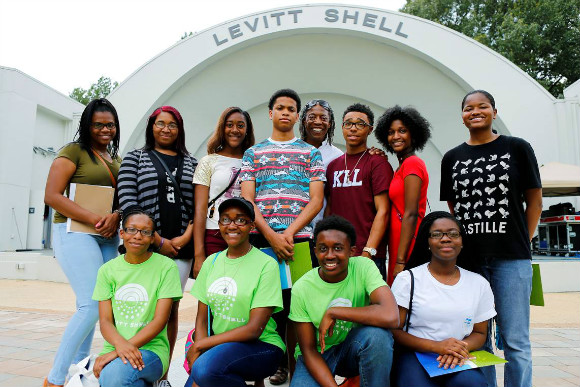 Nakia Poole (top row, next to last from left) stands with other Next Generation apprentices and Henry Nelson at the Levitt Shell.