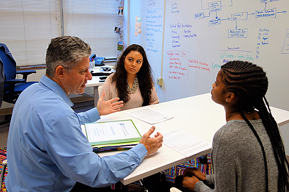 College students Cinthya Bolanos and Madisonne Cooper brainstorm with Scott Vogel.