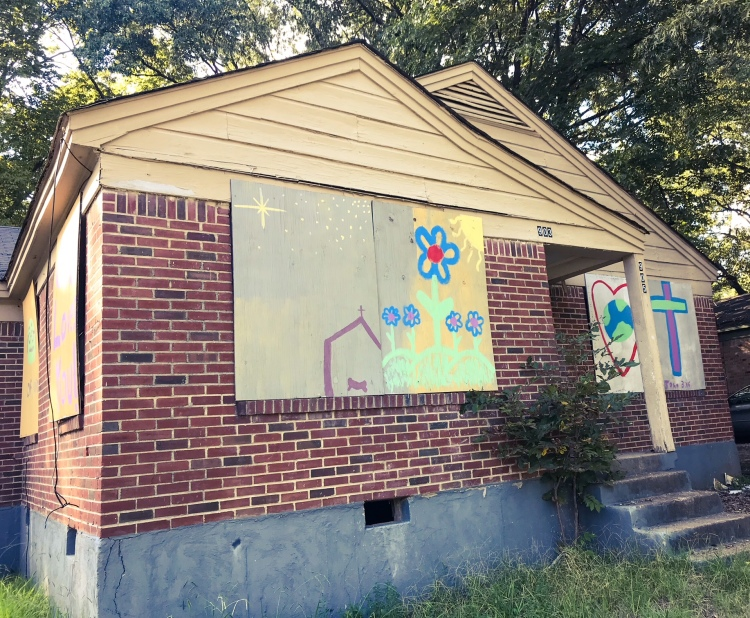 Community members boarded up a blighted house in Mitchell Heights and painted it with colorful artwork. (Cole Bradley)