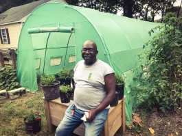 Sidney Johnson, president of the Mitchell Heights Neighborhood Association, poses in front of the hoop house at the Mitchell Heights Landscape Garden and Nursery. (Cole Bradley)