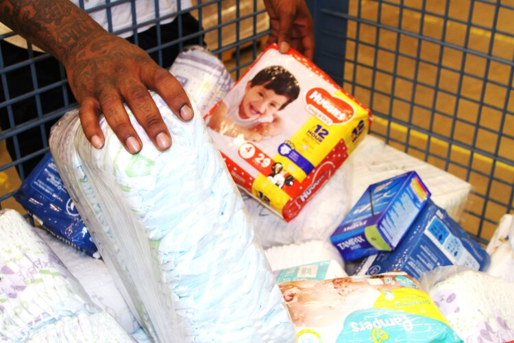 A volunteer sorts through a mix of diaper and period products donated to the Bare Needs Diaper Bank. (Mid-South Food Bank)
