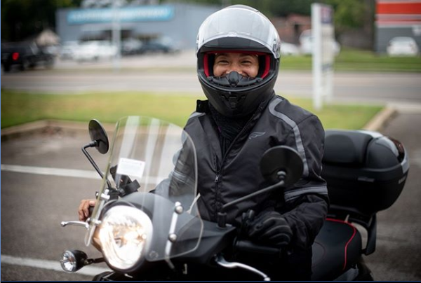 A rider, or Flyer, poses with a smile on a MyCityRide scooter. (MyCityRides)