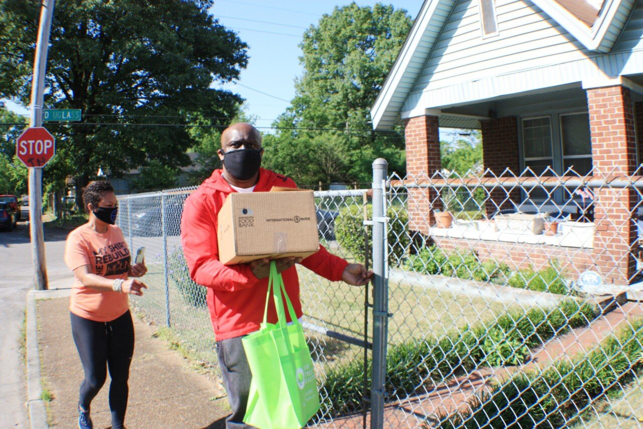 JUICE Orange Mound board members Kenya Holmes (L) and Broderick Conneser deliver supplies to a senior in Orange Mound. JUICE asked residents to text what supplies they needed and personalized orders before delivery via CAREavan. (Cole Bradley)