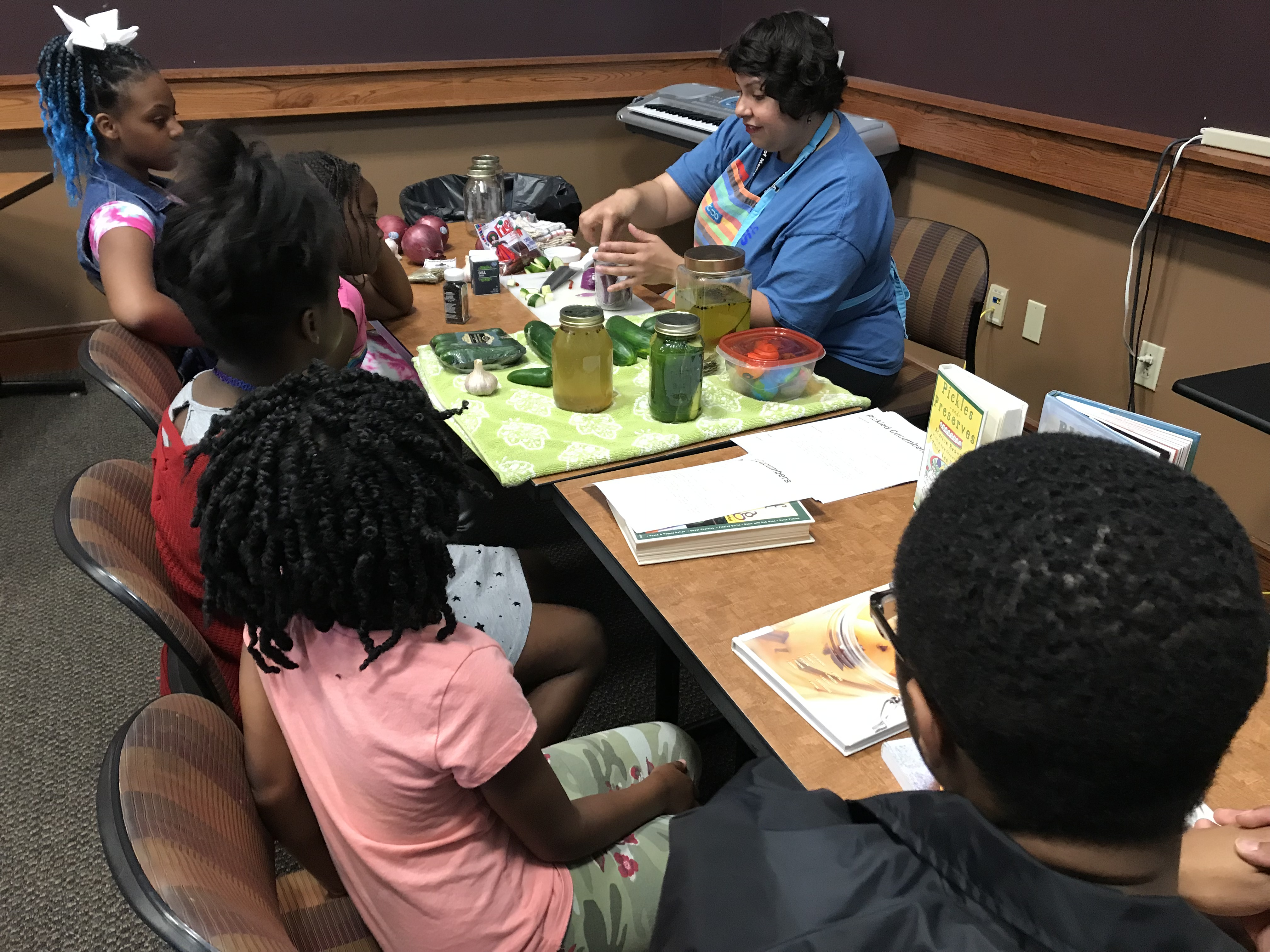 Melissa Sierra, Connect Crew manager for the Memphis Public Library system, talks about the process of making brine for a pickling class at the How-To-Festival, held at the Whitehaven Library on Saturday, April 27. (Kim Coleman)
