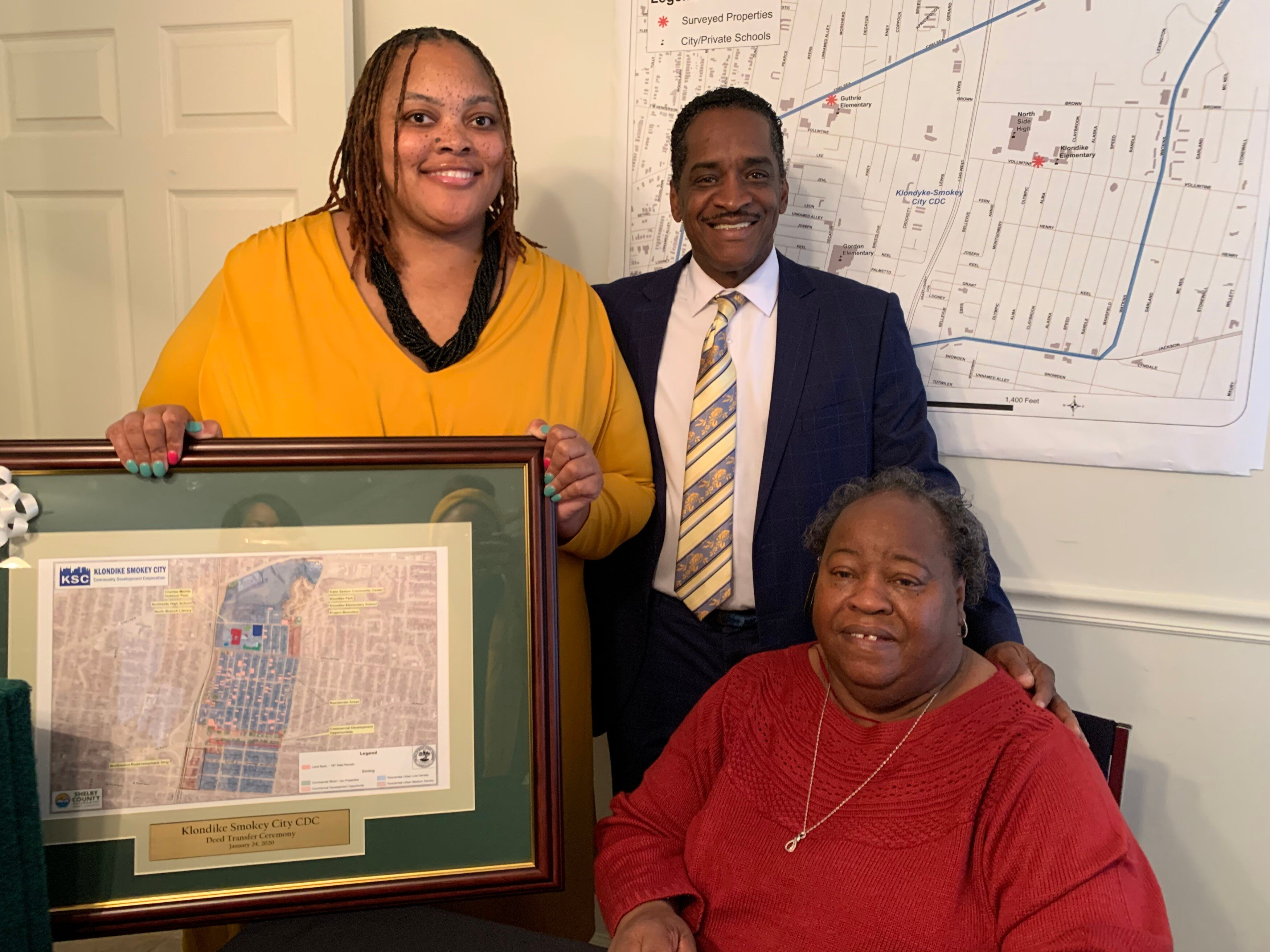 L to R: Shelby County Commissioner Tami Sawyer, Commissioner Eddie Jones, and Quincey Morris, executive director of the Klondike Smokey City CDC pose with a map of the 150 parcels transferred from the land bank to the CDC and NPI. (Ashlei Williams)