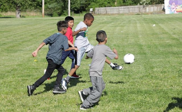 Children chase a soccer ball during an after-school game facilitated by Play Where You Stay. (Play Where You Stay)